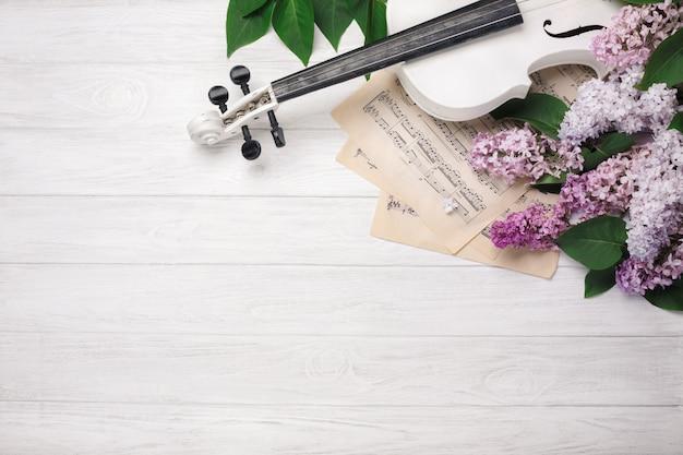 Ein blumenstrauß von fliedern mit violine und notenblatt auf einem weißen holztisch. top wiev mit platz für ihren text.
