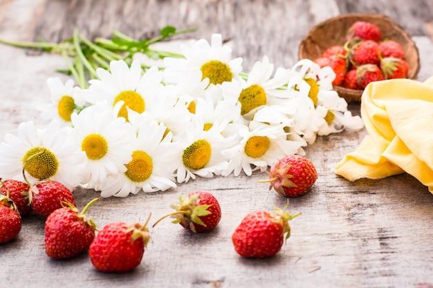 Ein blumenstrauß von gänseblümchen und von erdbeeren auf einem holztisch
