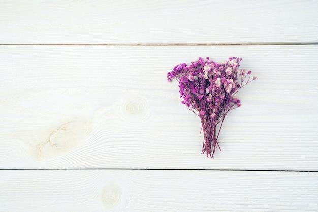 Ein blumenstrauß von lila blumen auf einem hellen hölzernen hintergrund. draufsicht mit platz zum kopieren.