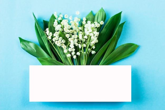 Ein blumenstrauß von maiglöckchen mit einem leerzeichen für text auf einem blauen hintergrund