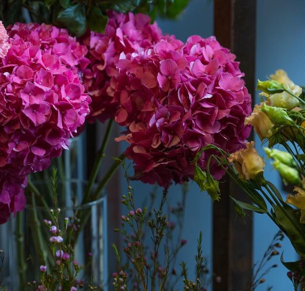 Ein blumenstrauß von rosa blumen mit grün verlässt innerhalb eines vase, der auf raumwand steht