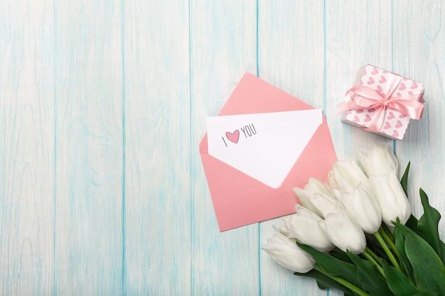 Ein blumenstrauß von weißen tulpen mit einer geschenkbox, einer liebesanmerkung und einem farbumschlag auf blauen hölzernen brettern