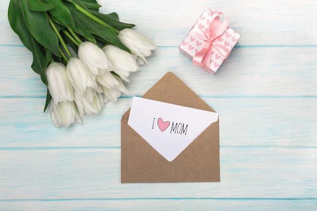 Ein blumenstrauß von weißen tulpen mit einer geschenkbox, liebesanmerkung und umschlag auf blauen hölzernen brettern. muttertag