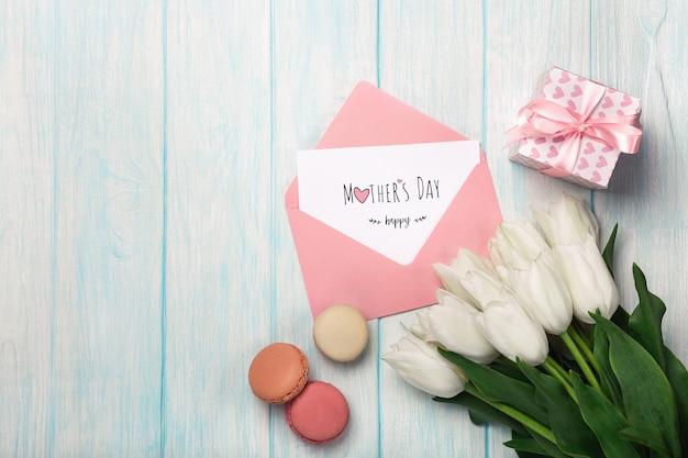 Ein blumenstrauß von weißen tulpen mit einer geschenkbox, macarons, liebesanmerkung und farbumschlag auf blauen hölzernen brettern. muttertag