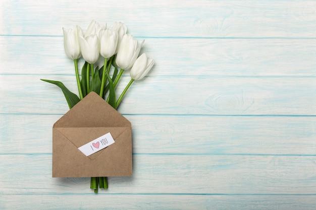 Ein blumenstrauß von weißen tulpen mit einer liebesanmerkung und einem umschlag auf blauen hölzernen brettern