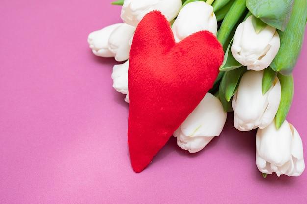 Ein blumenstrauß von weißen tulpen und von roten samtherzen auf einer rosa tabelle - das konzept des valentinstags.