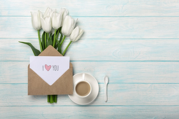 Ein blumenstrauß von weißen tulpen und von tasse kaffee mit einer liebesanmerkung auf blauen hölzernen brettern
