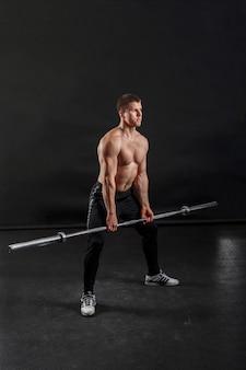 Ein bodybuilder posiert mit einer langhantel auf den knien