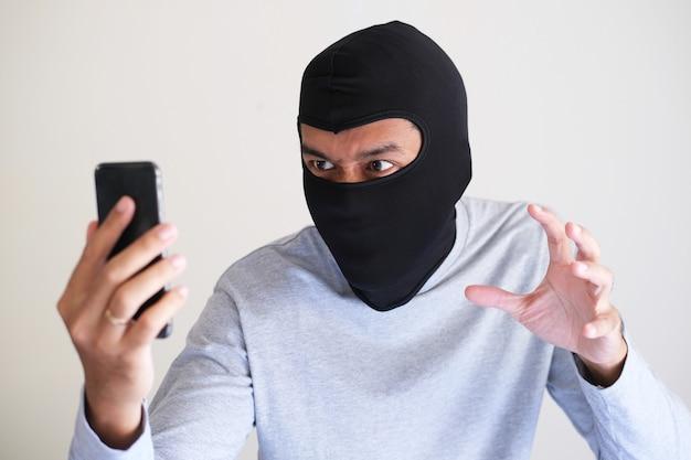 Ein bösewicht mit sturmhaube, der versucht, mit einem mobiltelefon persönliche daten von jemandem zu stehlen