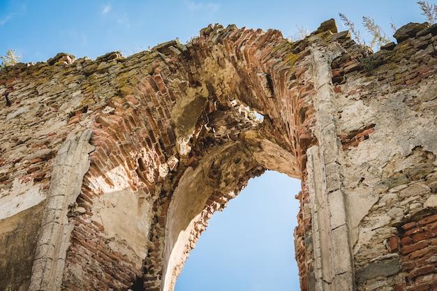 Ein bogen in der zerstörten mauer der mittelalterlichen burg