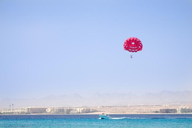 Ein boot auf dem blauen meer zieht einen roten fallschirm