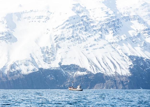 Ein boot im meer mit erstaunlichen felsigen schneebedeckten bergen
