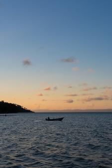 Ein boot in der mitte der bucht mit einem sonnenuntergang dahinter