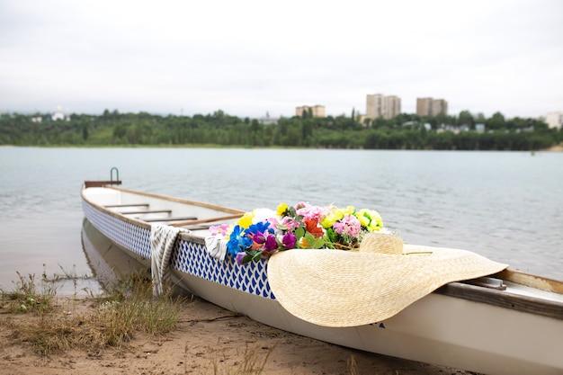 Ein boot mit blumen und einem hut am flussufer an einem sommertag