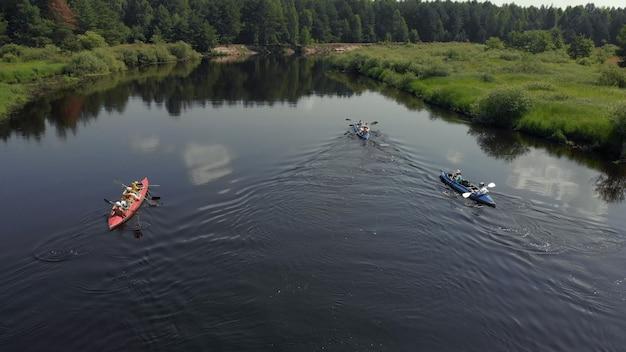 Ein boot verfolgen. touristenbasis für kajaks und kanus, sommer-abenteuer-kajak, rafting zum kanu. kajak-draufsicht. gruppe kajaks, die zusammen rudern. luftbild von der drohne.