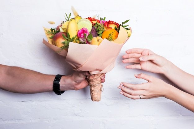 Ein bouquet von früchten und blumen wird von einem mann gegeben