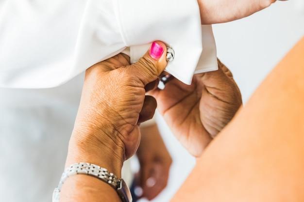 Ein bräutigam, der manschettenknöpfe anlegt, während er sich an seinem hochzeitstag anzieht. bräutigam anzug