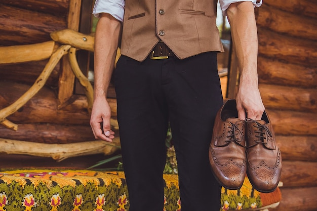 Ein bräutigam und hochzeitsschuhe. der bräutigam trägt schuhe im freien. männliches porträt des gutaussehenden kerls.