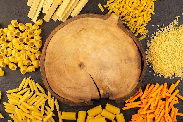 Ein brauner holzschreibtisch der draufsicht zusammen mit verschiedenen geformten gelben rohen nudeln, die auf der dunkelheit isoliert werden