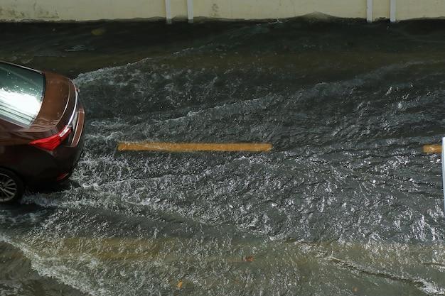 Ein braunes auto fährt durch überflutete straßen. weicher fokus. transport- und umweltkonzept.