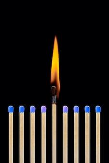 Ein brennendes match in einer gruppe von blau entspricht dem konzept der führung, der entstehung einer idee