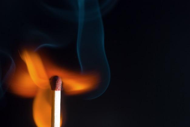 Ein brennendes streichholz auf schwarzem hintergrund