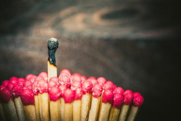 Ein brennendes streichholz hebt sich von der masse ab