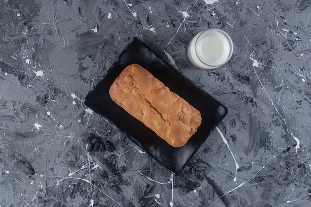 Ein brett mit frisch gebackenem rosinenbrot auf einer marmoroberfläche.