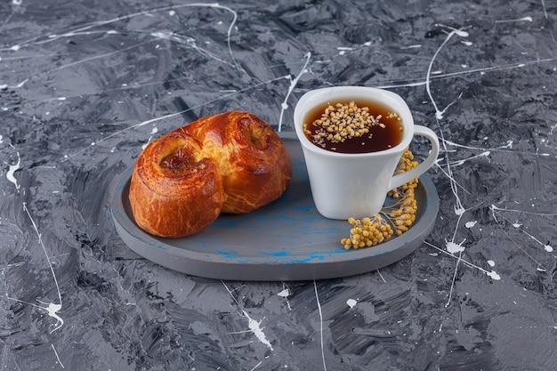 Ein brett mit süßem, verdrehtem gebäck und einer tasse tee auf einer marmoroberfläche.