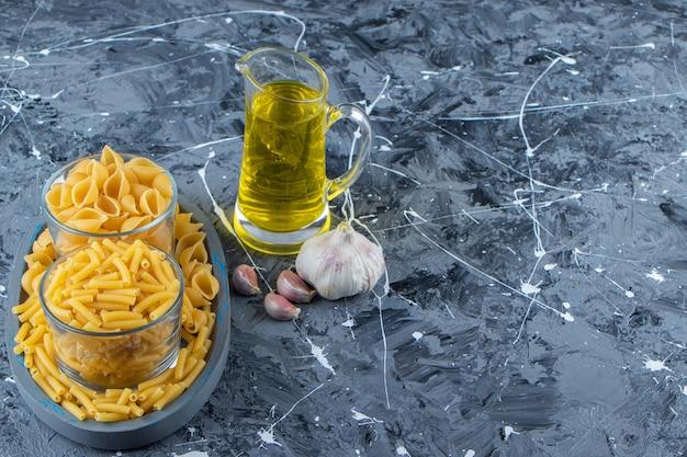 Ein brett von zwei arten von rohen makkaroni mit gemüse und öl auf einem marmorhintergrund.