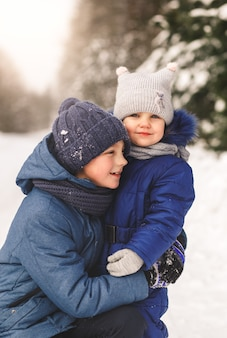Ein bruder umarmt seine kleine schwester im winter in der natur. glückliche kinder zusammen