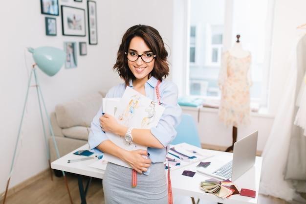 Ein brünettes mädchen in einem grauen kleid und einem blauen hemd steht nahe dem tisch in einem werkstattstudio. sie hält skizzen in den händen. sie geht in die kamera.