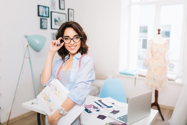 Ein brünettes mädchen in einem grauen kleid und einem blauen hemd steht nahe dem tisch in einem werkstattstudio. sie hält skizzen in einer hand und eine brille in der anderen. sie lächelt in die kamera.