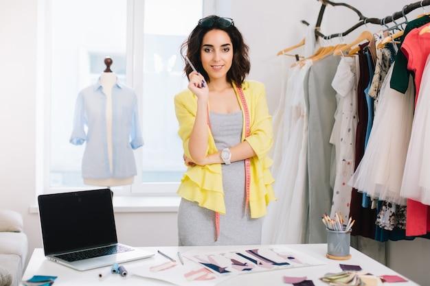 Ein brünettes mädchen in einem grauen kleid und einer gelben jacke steht in einem werkstattstudio neben dem tisch. sie hat viele kreative sachen auf dem tisch. sie hält einen bleistift in der hand.
