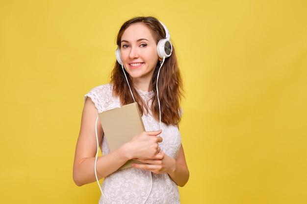 Ein brünettes mädchen in sommerkleidung hört abstrakt ein hörbuch mit kopfhörern.