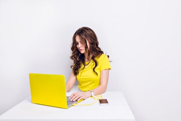 Ein brünettes mädchen mit lockigem haar sieht frustriert aus, als es vor dem laptop im gelben fall sitzt.