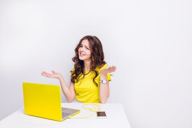 Ein brünettes mädchen mit lockigem haar sieht verwirrt aus, wenn es vor dem laptop im gelben fall sitzt.