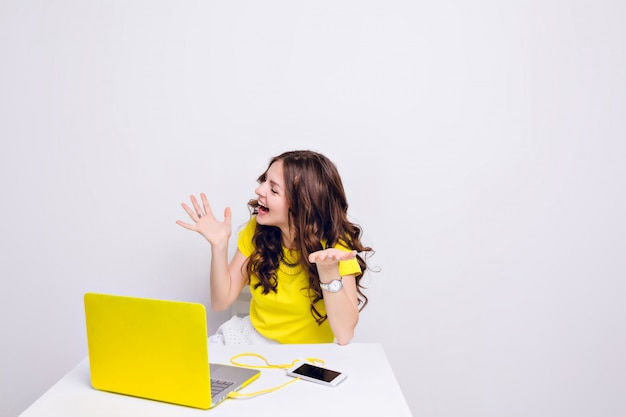 Ein brünettes mädchen mit lockigem haar spielt albern vor einem laptop im gelben fall.