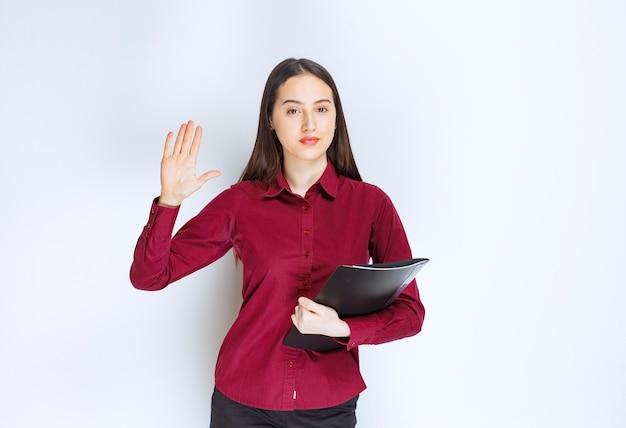 Ein brünettes mädchenmodell, das mit einem ordner steht und mit den fingern nach oben zeigt.