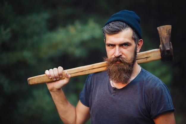 Ein brutaler bärtiger mann mit einem schnurrbart in einem warmen hut und einem blauen hemd hält eine axt auf der schulter