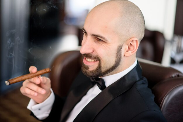 Ein brutaler mann im frack raucht eine zigarre.