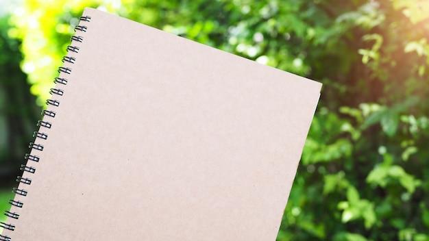 Ein buch für notizen oder zum arbeiten hat eine braune abdeckung im garten mit einem grünen baum als hintergrund.