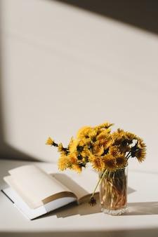 Ein buch und ein haufen gelber löwenzahn