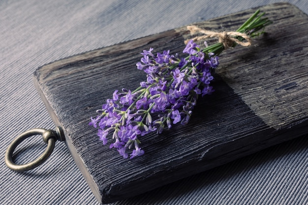 Ein bündel blühender lavendel auf einem hölzernen schneidebrett. konzept der traditionellen medizin, kosmetik oder aromatherapie