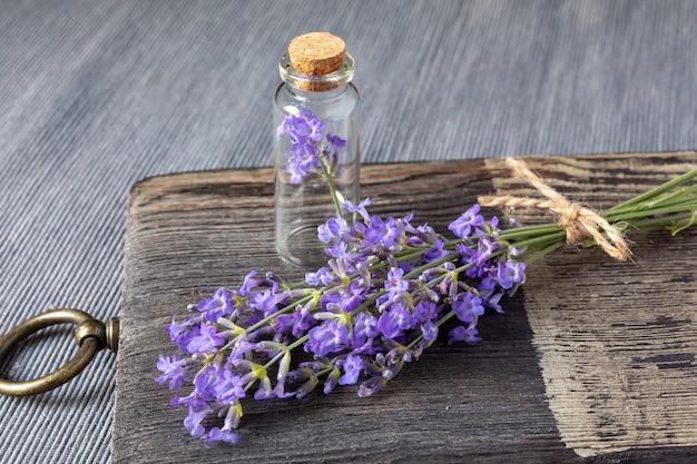 Ein bündel blühender lavendel und eine kleine glasflasche mit korkdeckel auf einem holzschneidebrett. konzept der traditionellen medizin