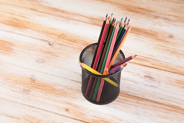 Ein bündel buntstifte in einem ständer auf einem tisch