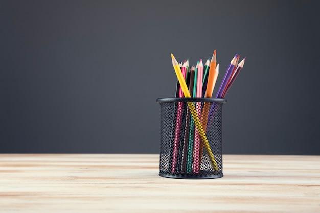Ein bündel buntstifte in einem stand auf einer grauen szene