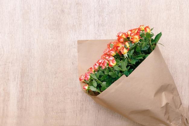 Ein bündel der frischen herrlichen rosen im bastelpapier auf einem hölzernen hintergrund