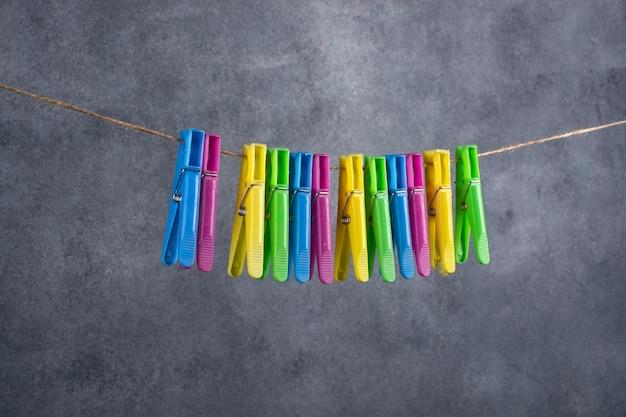 Ein bündel farbiger plastikwäscheklammern hängt an einem seil.