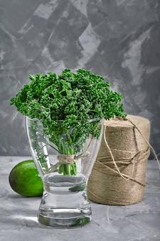 Ein bündel frische, lockige petersilie in einer vase mit wasser. back layout mit umweltfreundlicher verpackung
